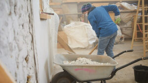 Removing lime plaster from strawbale walls.